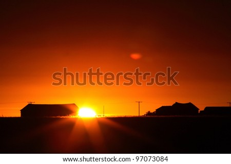 Sun rising behind a Saskatchewan farm building