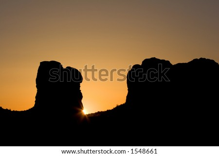 Sun rising behind desert butte - Arches National Park, USA.