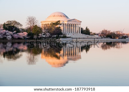 Sun rising illuminates the Jefferson Memorial and Tidal Basin with calm water of Tidal Basin reflecting the monument - stock photo