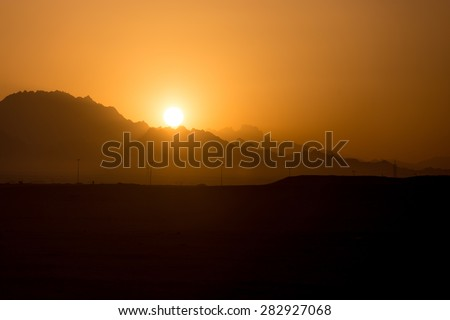 Sun rising or setting in mountains, beautiful mountainous landscape sunlit in shades of orange and gold - stock photo