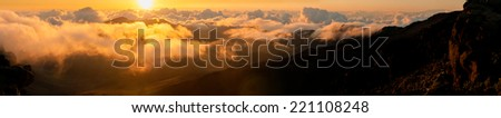 Sun rising over clouds at sunrise from on top of Haleakala Crater, Maui, Hawaii, USA - stock photo