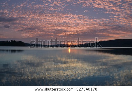 Sun rising over Lake of Two Rivers  in Algonquin Park, Canada. - stock photo