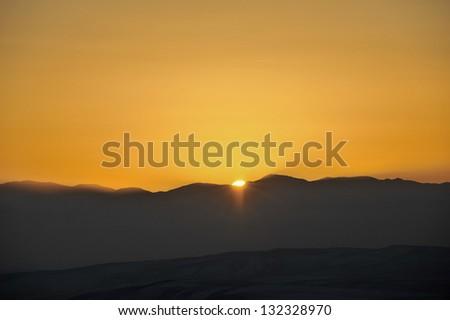 Sun set behind the mountains - stock photo