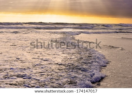Sun sets above the ocean, tidal waves and dramatic sky