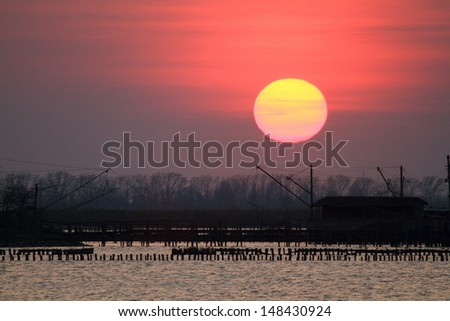 sun sets on the marshes of the delta of po - stock photo