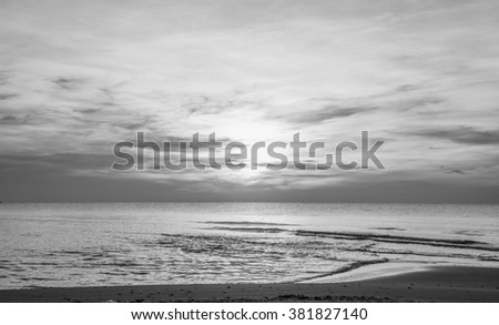 Sun sets over horizon of ocean. Sky, water and shore in the evening paint. Monochrome - stock photo