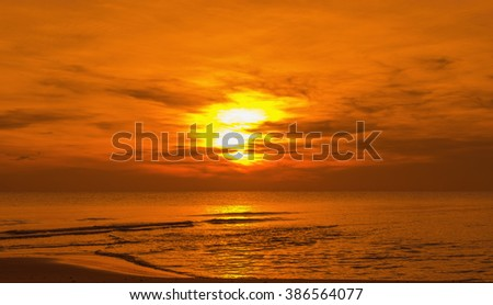 Sun sets over horizon of ocean. Sky, water and shore in the evening painted in orange color.