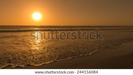 Sun sets over horizon of ocean. Surf on sandy beach. Sky, water and shore in the evening painted in orange, gold color. - stock photo
