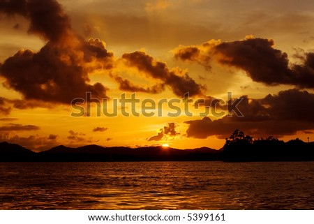 Sun sets over horizon with ocean in foreground