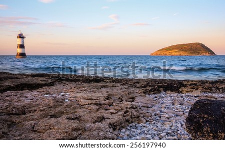 Sun sets over Puffin Island, Anglesey, North Wales as seen from Penmon Point - stock photo
