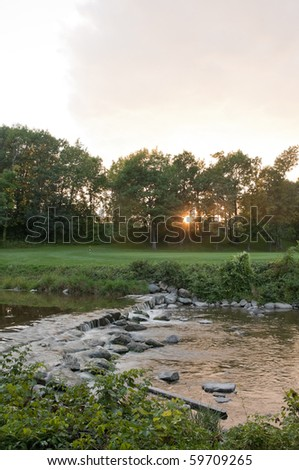 Sun setting down on the golf course - stock photo