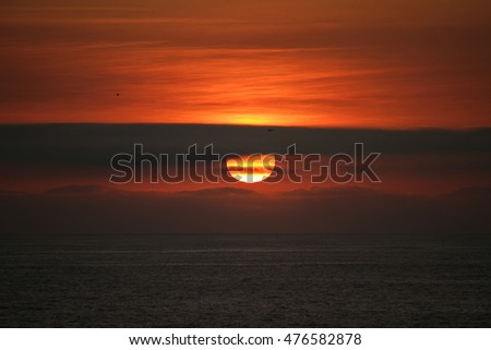 sun setting in clouds over ocean
