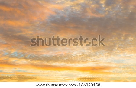 Sun setting in the early evening reflecting orange on the clouds - stock photo