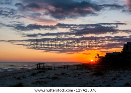 Sun setting on the beach with houses and pier