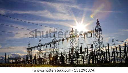 Sun setting over an electrical substation. - stock photo