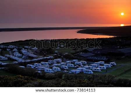 Sun setting over coastal caravan park in Dorset England - stock photo