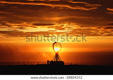 Sun setting over globe sculpture in Nord Cap, the most northen point of Europe