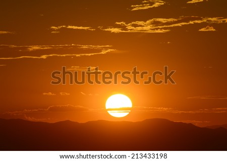 Sun setting over hills on horizon - stock photo