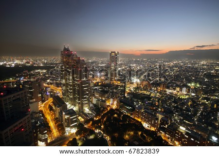 Sun setting over light up buildings and skyscrapers in Tokyo, Japan - stock photo