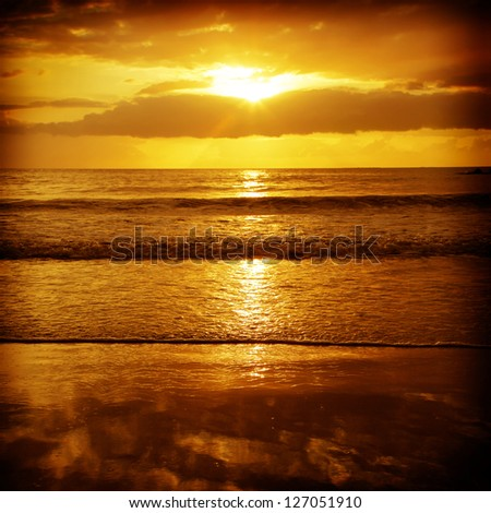 Sun setting over the ocean. - stock photo