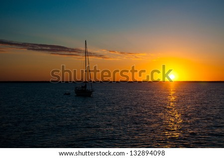 Sun setting over the ocean on a beautiful night with a sailboat anchored in the water.  copy space available - stock photo