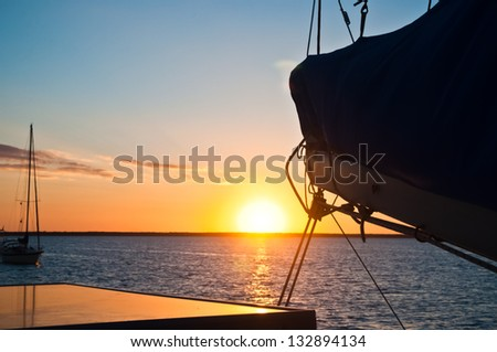 Sun setting over the ocean with the boom and mainsail of a sailboat in the foreground and another sailboat anchored in the distance copy space available - stock photo