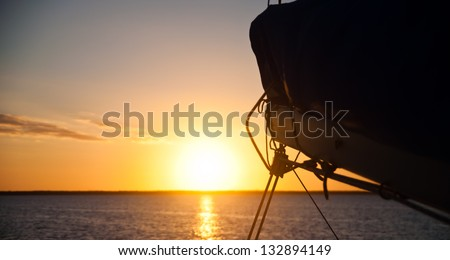 Sun setting over the ocean with the boom and mainsail of a sailboat in the foreground.  copy space available