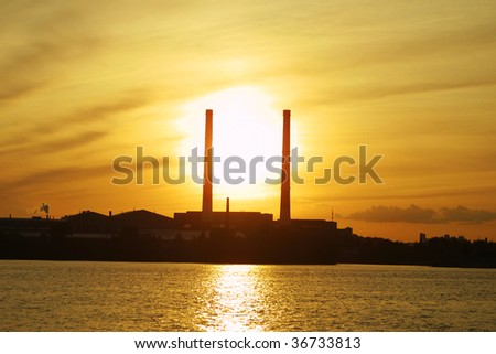 Sun settings behind power plant pipes