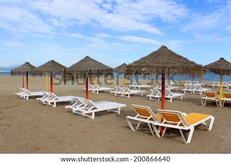Sun shades and empty loungers in the sandy beach of Torremolinos, Costa Del Sol, Andalusia, Spain in late afternoon