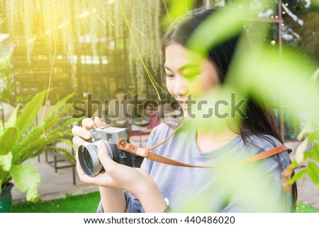 Sun shine of attractive young asian woman talking pictures outdoors cafe park - stock photo