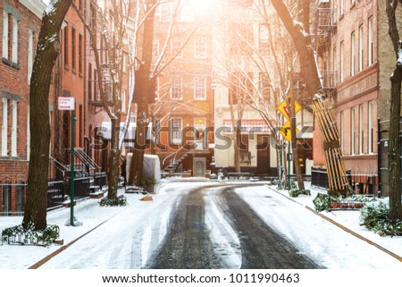 Sun shines on snow covered Commerce Street after a winter storm in Greenwich Village Manhattan New York City