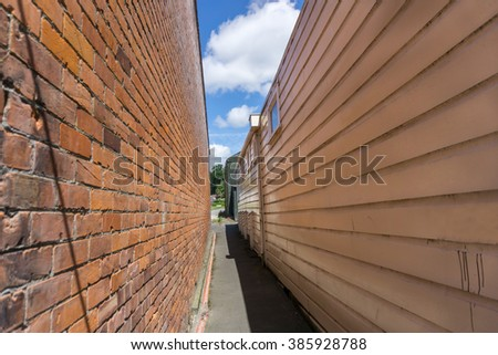 Sun shines on wall one side of narrow walkway between two buildings one brick wall one wooden wall in shade