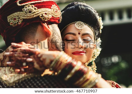 Sun shines over the beautiful Indian bride closing her eyes while hugging a groom