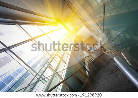 Sun shining modern office building stairway glass - stock photo