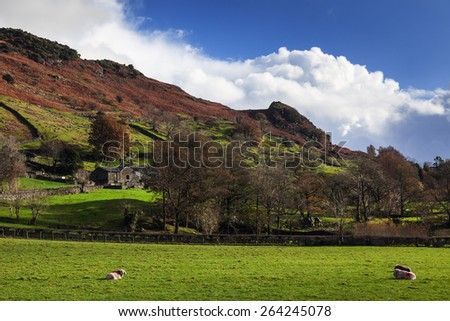 Sun shining on the Upper Langdale Valley. This view captures a rare sunny moment during a cloudy day in the lovely Upper Langdale Valley. - stock photo
