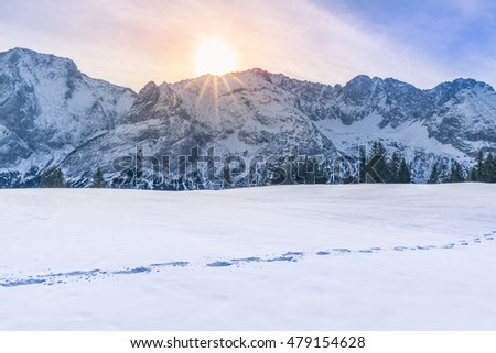 Sun shining over mountain peaks and snow