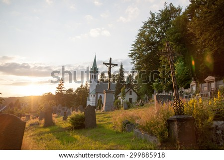sun shining through clouds to sad melancholic christian cemetery near forrest during sunset