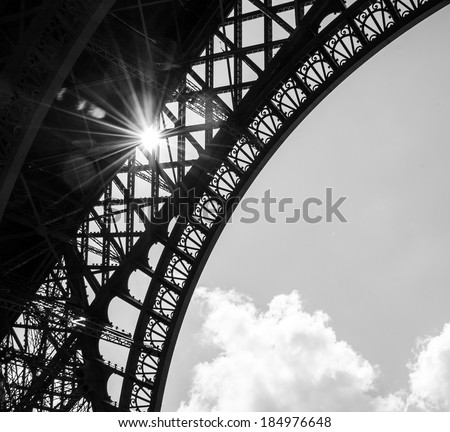 Sun shining through Eiffel Tower. Sun beams and spots. Aged photo. Black and white. - stock photo