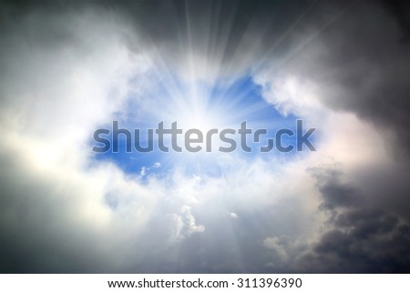 sun shining through hole in the dark clouds - stock photo