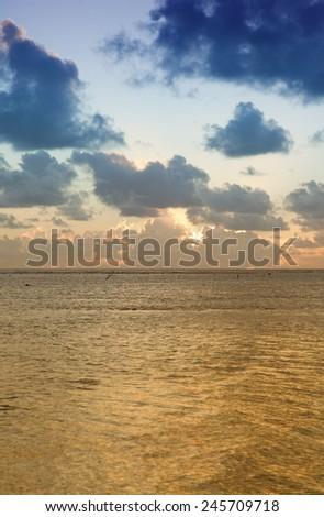 Sun sinks to Sea under a cloud-filled Sky at Sunset - Rarotonga, Cook Islands, Polynesia - stock photo