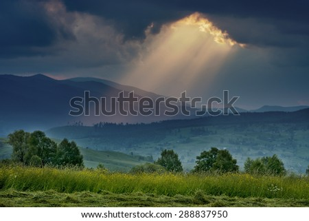 sun through the clouds in the foreground grass and trees on the horizon Mountain - stock photo