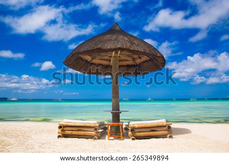 Sun umbrella and beach beds on tropical beach. Summer vacantion concept. - stock photo