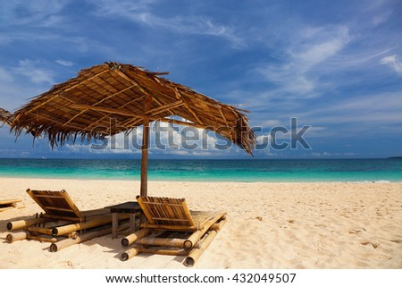 Sun umbrella and beach beds on tropical beach. Summer vacation concept.