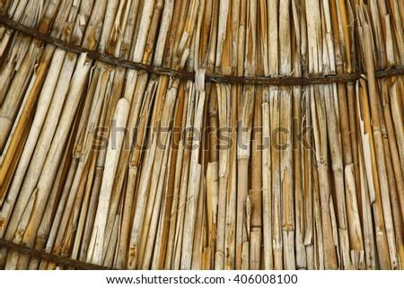 Sun umbrella textured background. Grass roof. Macro beach umbrella. Bamboo umbrella. Closeup texture of straw beach umbrella. - stock photo