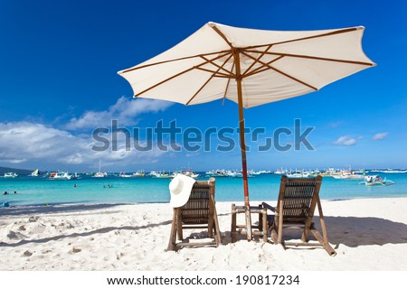 Sun umbrella with chair longue on tropical beach