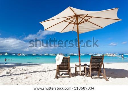 Sun umbrella with Summer Hat on chair longue - stock photo