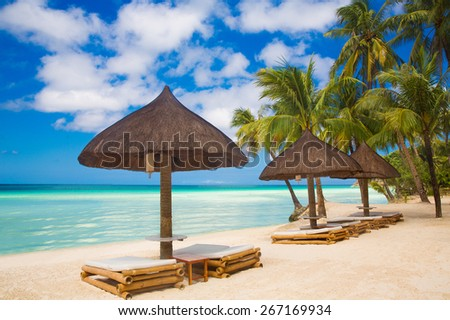Sun umbrellas and beach beds under the palm trees on tropical beach. Summer vacantion concept. - stock photo