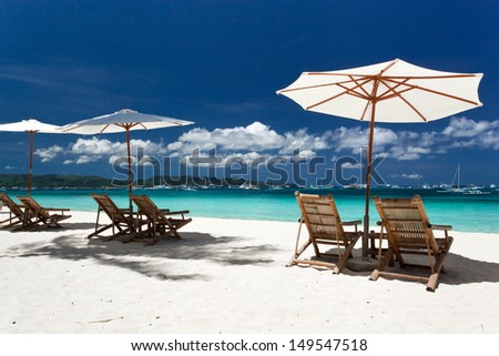 Sun umbrellas and beach chairs on tropical beach, Philippines