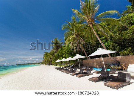Sun umbrellas and beach chairs on tropical coast, Boracay