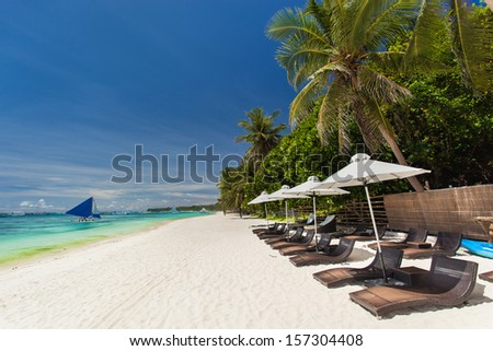 Sun umbrellas and beach chairs on tropical coastline, Philippines, Boracay  - stock photo